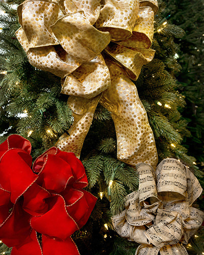 Closeup shot of a Christmas tree decorated with three oversized bows
