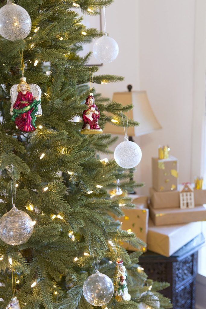 Closeup shot of globe-shaped ornaments and Christmas figurines hanging from a Christmas tree