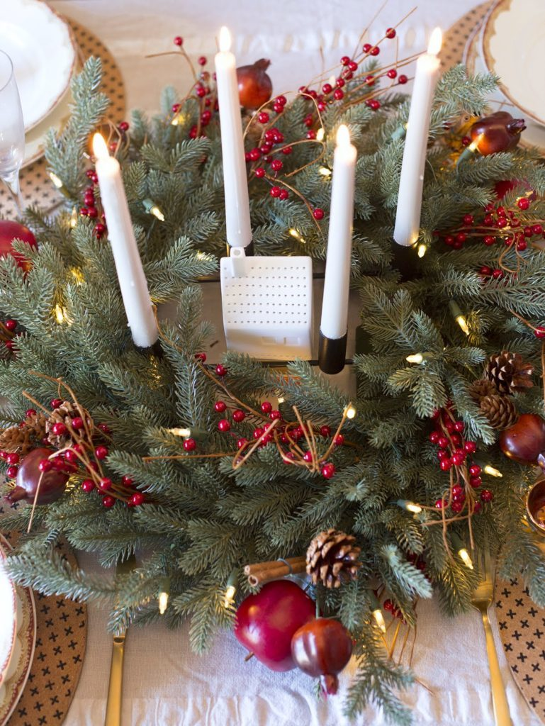 Four candlesticks placed atop an artificial wreath on a table