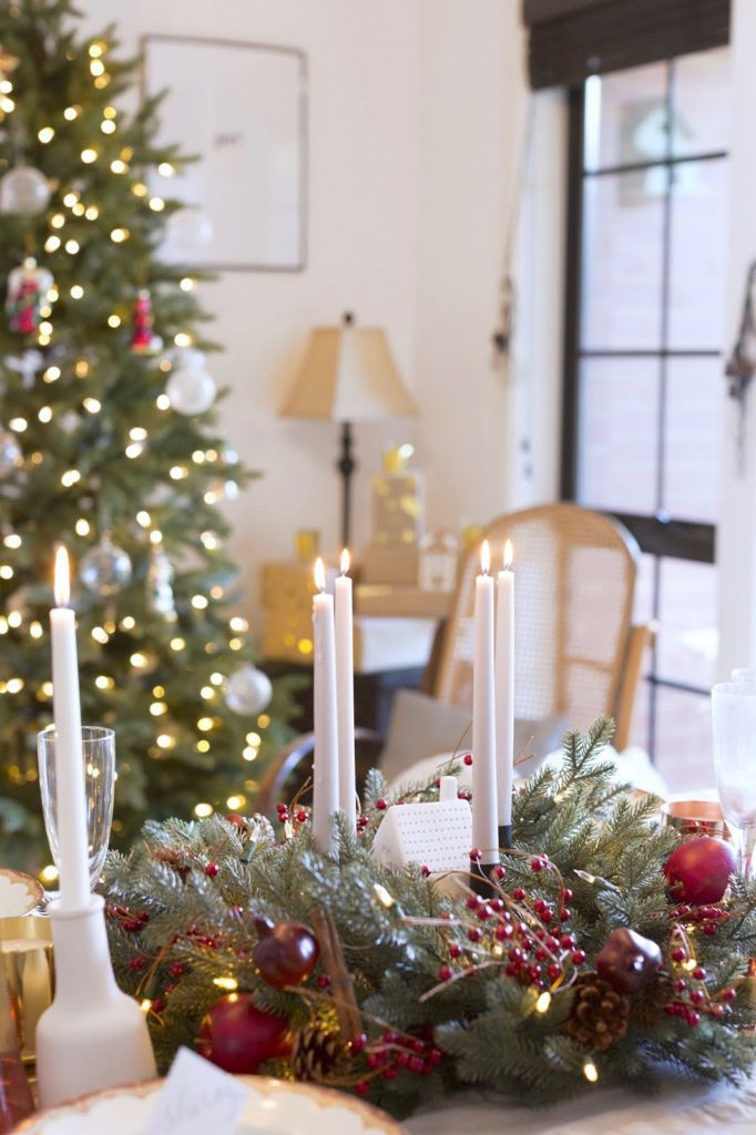 Closeup shot of a table setting with candlesticks, glasses, and artificial greenery