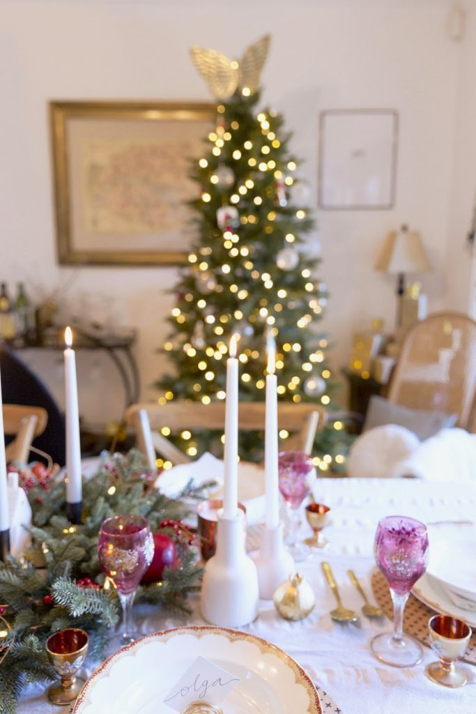 Closeup shot of a table setting with three candlesticks and a wreath