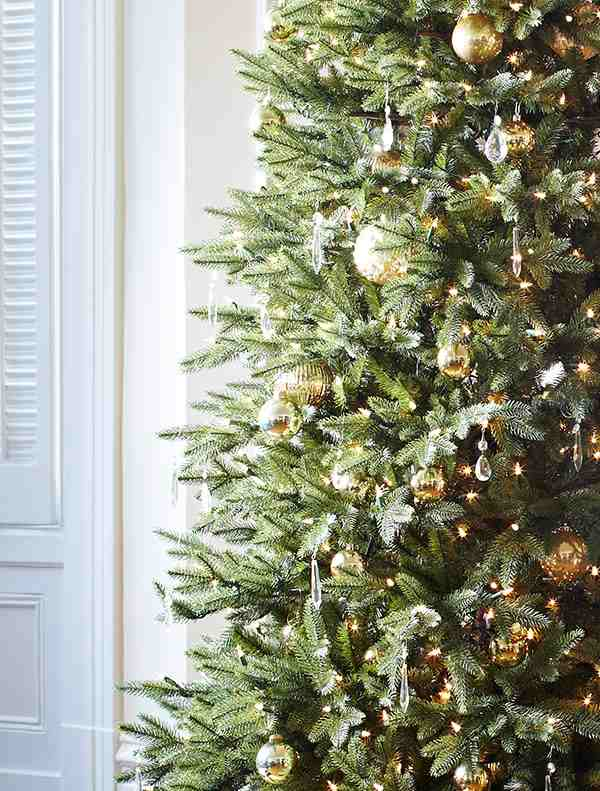 Closeup of Elegant Artificial Christmas Tree decorated with silver and gold balls and crystal ornaments