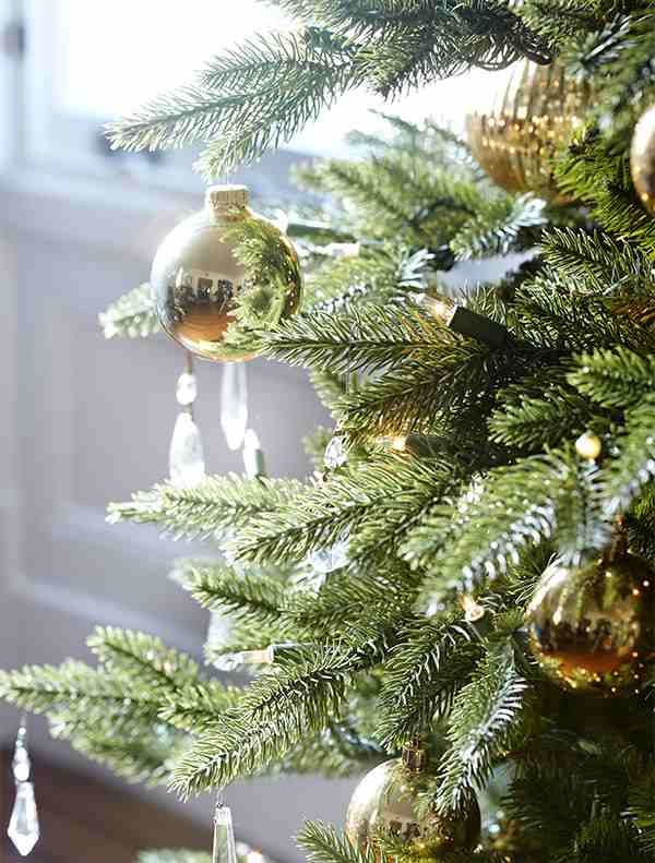 Closeup of Elegant Christmas Tree decorated with gold balls and crystal ornaments