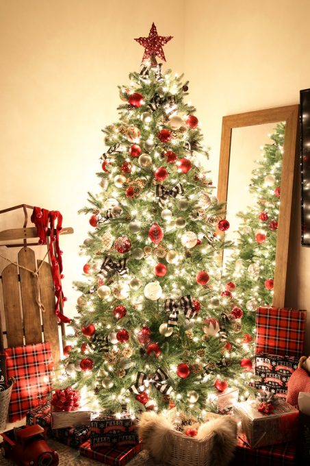 Pre-lit artificial Christmas tree decorated with red, white, and black ornaments beside a mirror and a sled