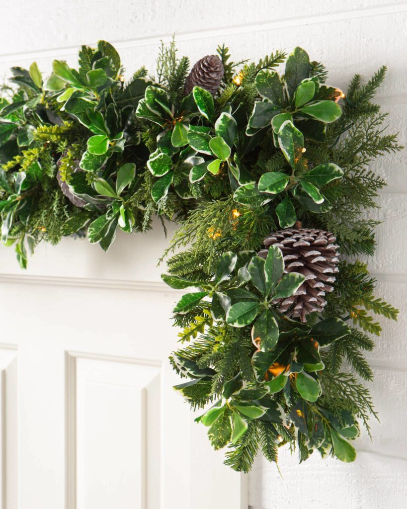Balsam Hill Outdoor Woodland Evergreen Garland on top of door frame