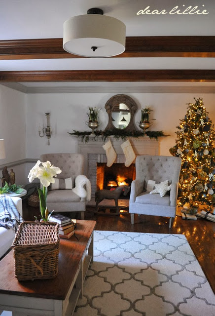 Living room and fireplace with neutral colored furniture, carpet, and carpet, and a pre-lit Christmas tree