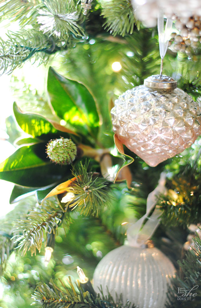 Closeup shot of metallic ornaments hanging from a Christmas tree