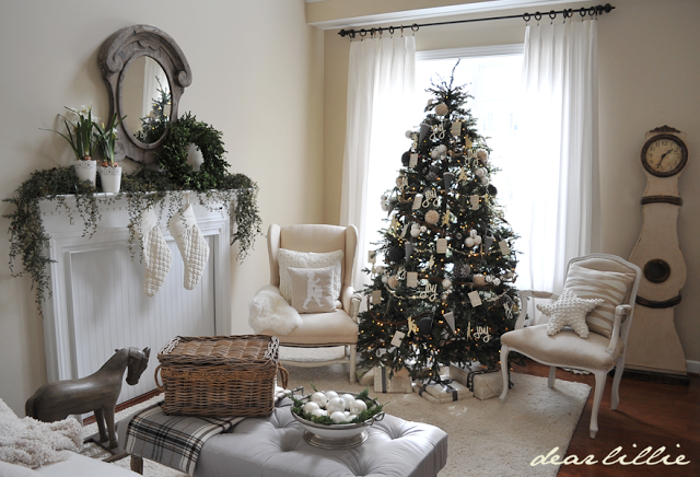 Fireplace living room with neutral colored furniture and a Balsam Hill Christmas tree decorated with little drummer boy cutouts, glistening balls, and dried hydrangeas