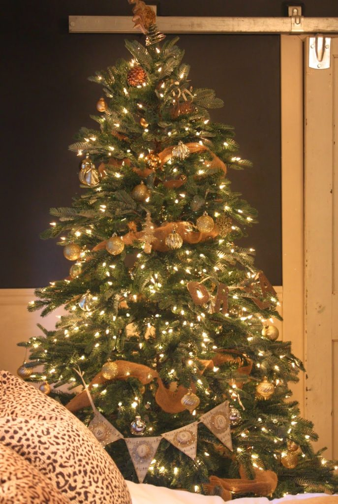 A lit-up Christmas tree decorated with assorted ornaments and burlap ribbons