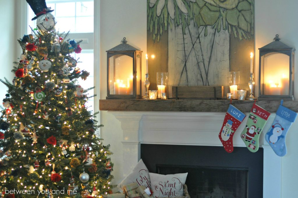 Pre-lit Christmas tree decorated with snowman-themed ornaments beside fireplace mantel