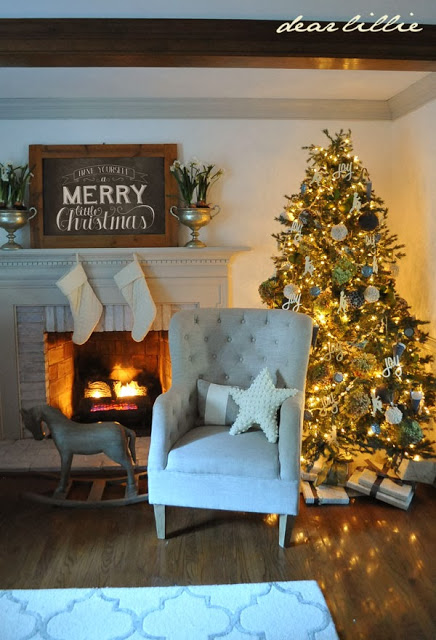Fireplace with neutral Christmas decorations and a neutral colored sofa with a pre-lit Balsam Hill tree at the back