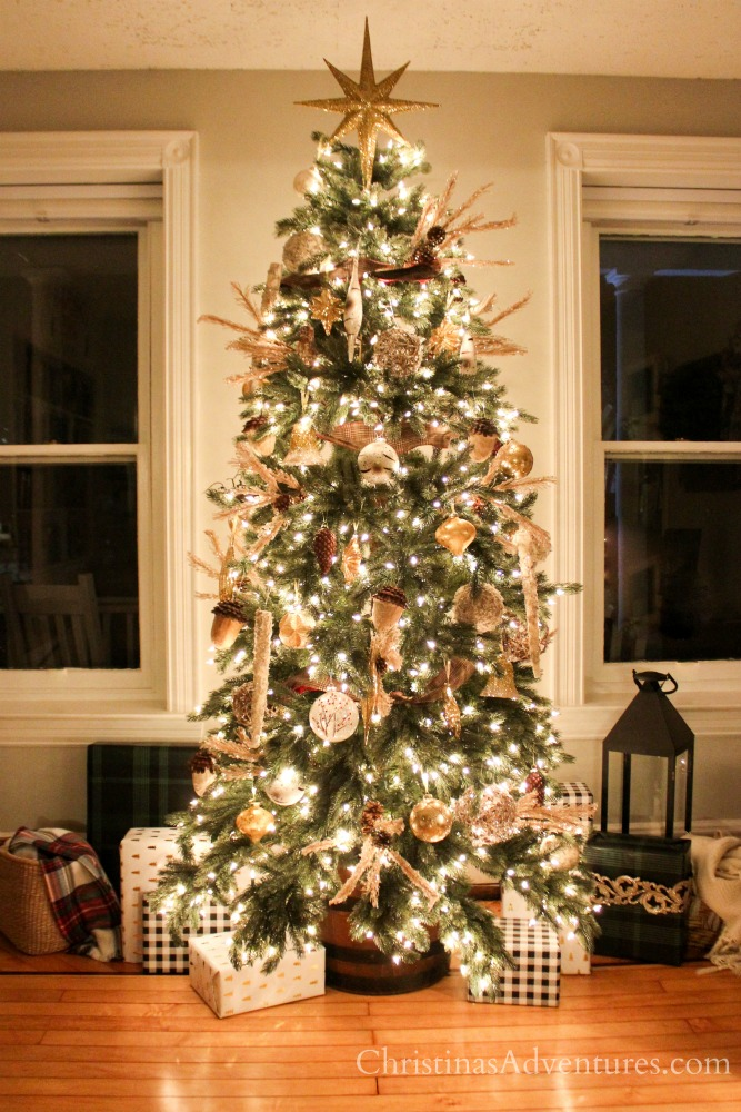 Vermont White Spruce Narrow artificial pre-lit Christmas tree decorated with gold and silver ornaments, pinecones, berry picks, and star tree topper