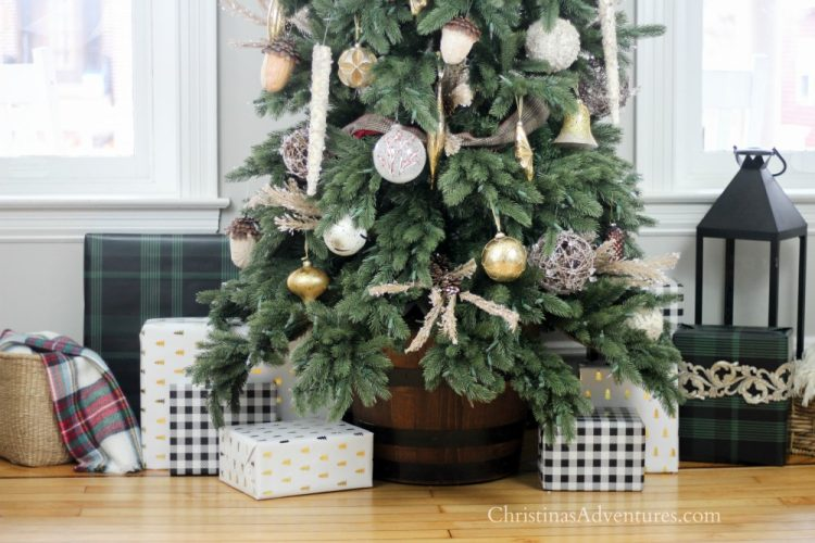 Vermont White Spruce Narrow artificial Christmas tree decorated with gold and silver ornaments, pinecones, berry picks, and rolling tree stand