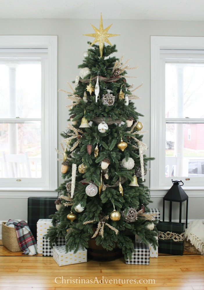 Vermont White Spruce Narrow artificial Christmas tree decorated with gold and silver ornaments, pinecones, berry picks, and star tree topper