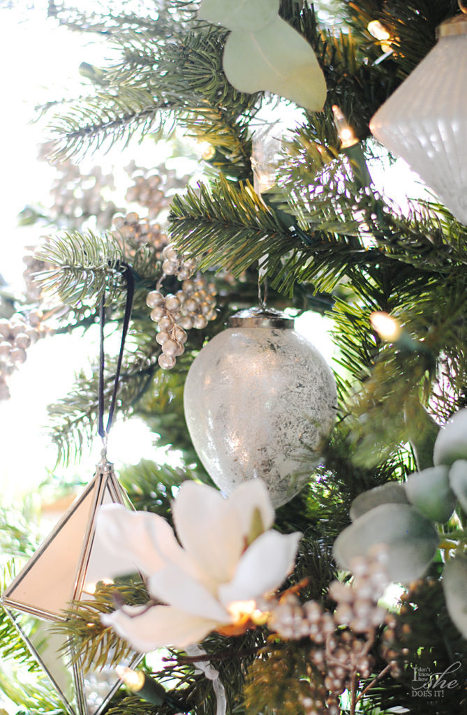 Closeup shot of a Christmas tree decorated with white metallic ornaments and tree picks.
