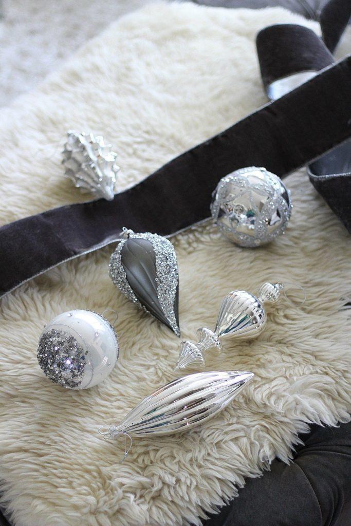 Closeup shot of assorted silver ornaments and a black ribbon