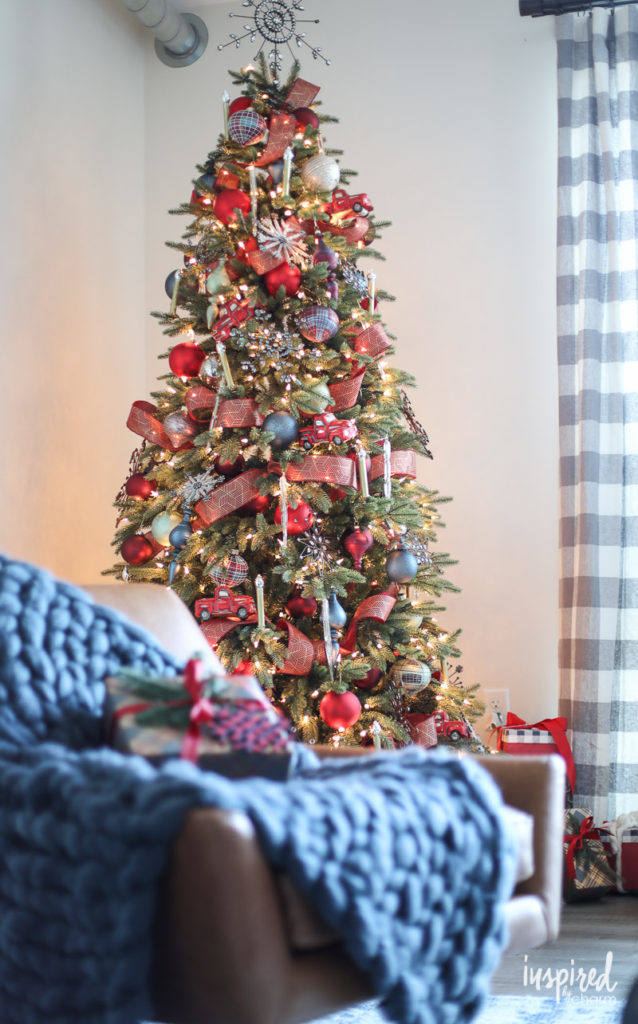 Pre-lit artificial Christmas tree decorated with ornaments, ribbon, and tree picks
