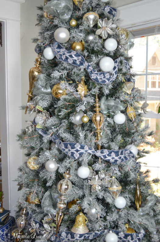 close up of frosted christmas tree decorated with white ornaments and blue ribbon
