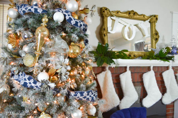 close up of decorated frosted christmas tree with blue ribbon and white, silver, gold ornaments