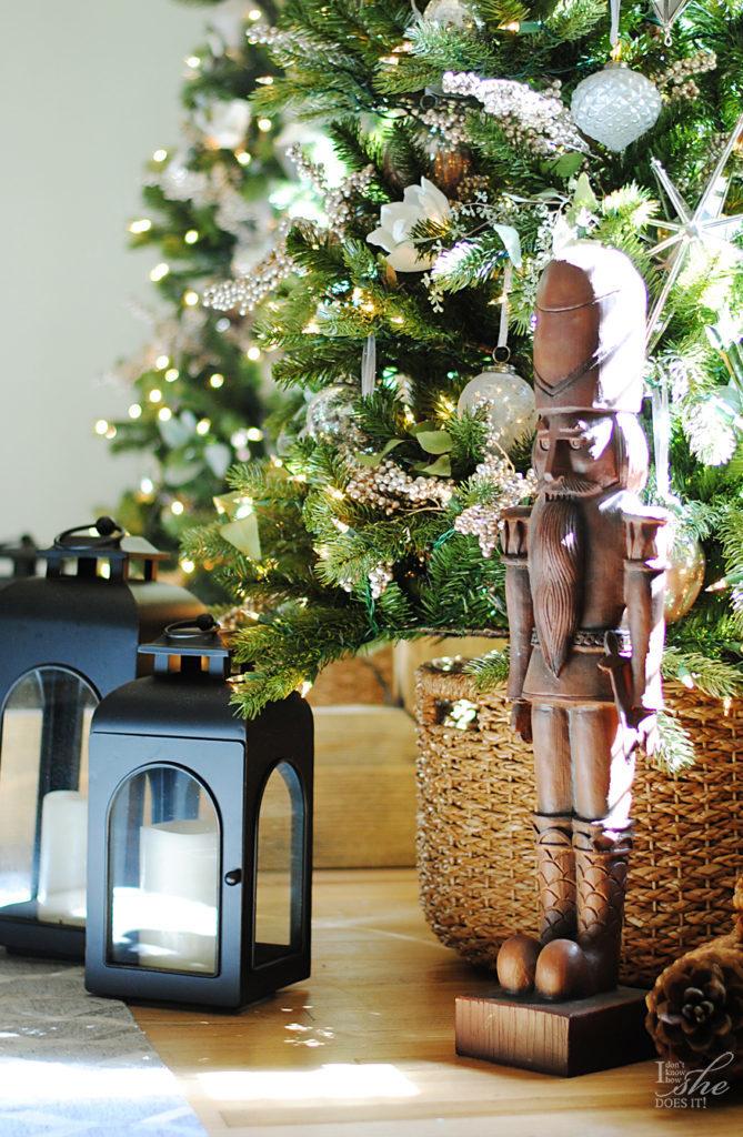 Closeup shot of a nutcracker figure placed beside a Christmas tree