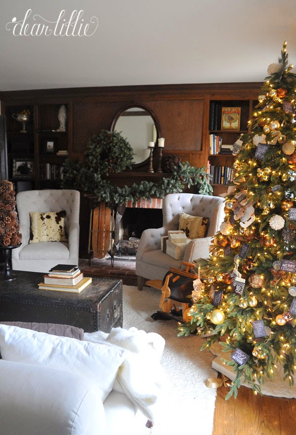 A living room with a lit-up Christmas tree to the right
