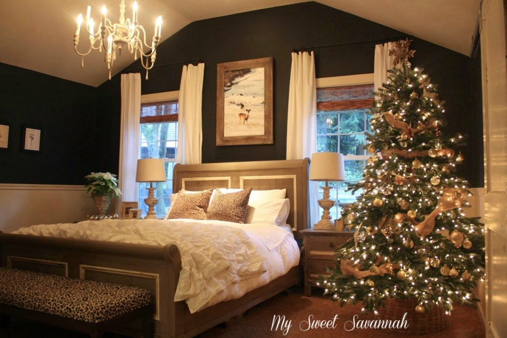 A bedroom with a lit-up Christmas tree by the window