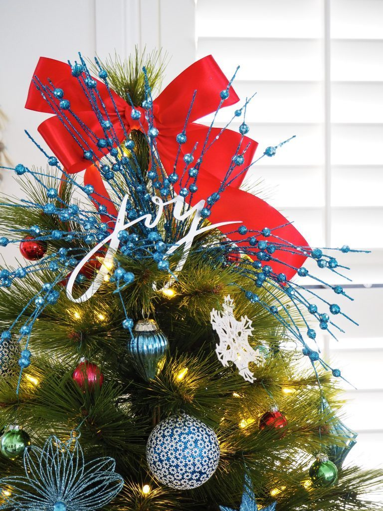 pine tree with red ribbon topper