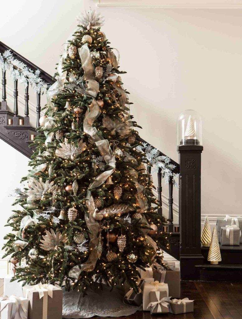 A lit-up Christmas tree decorated with assorted white and metallic ornaments