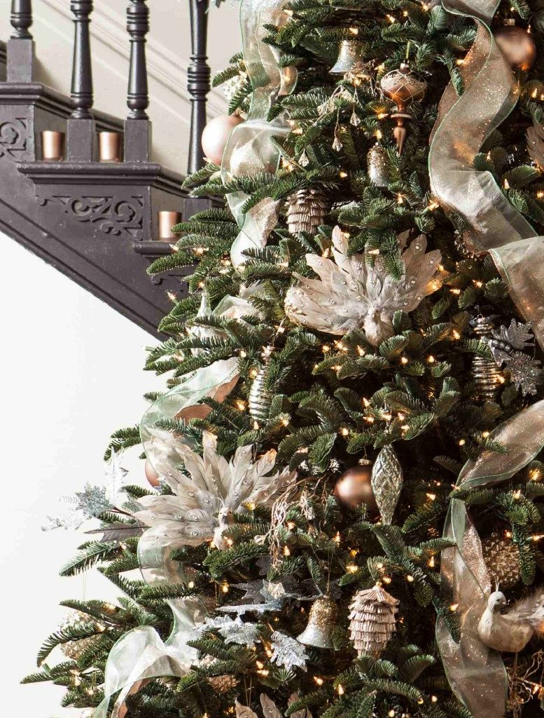 Closeup shot of a lit-up Christmas tree decorated with assorted white and metallic ornaments