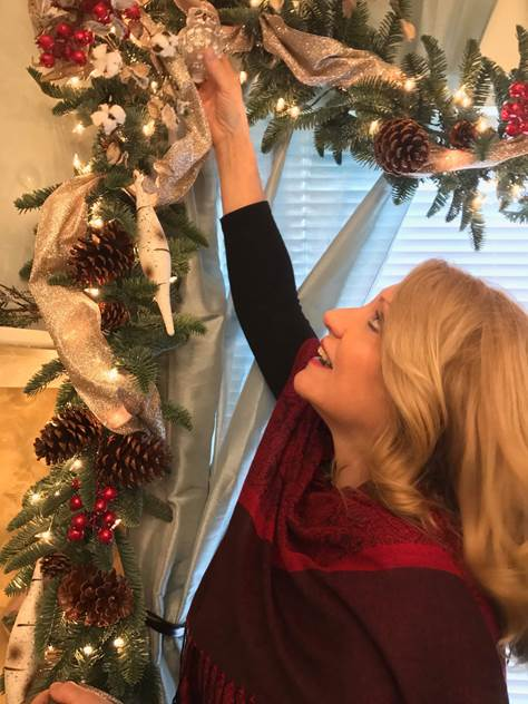 A woman reaching for an ornament attached to a Christmas garland