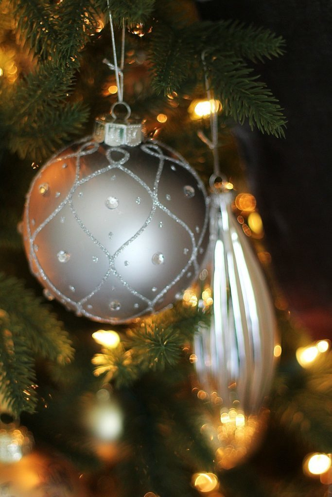 Closeup shot of silver metallic ornaments hanging from a Christmas tree