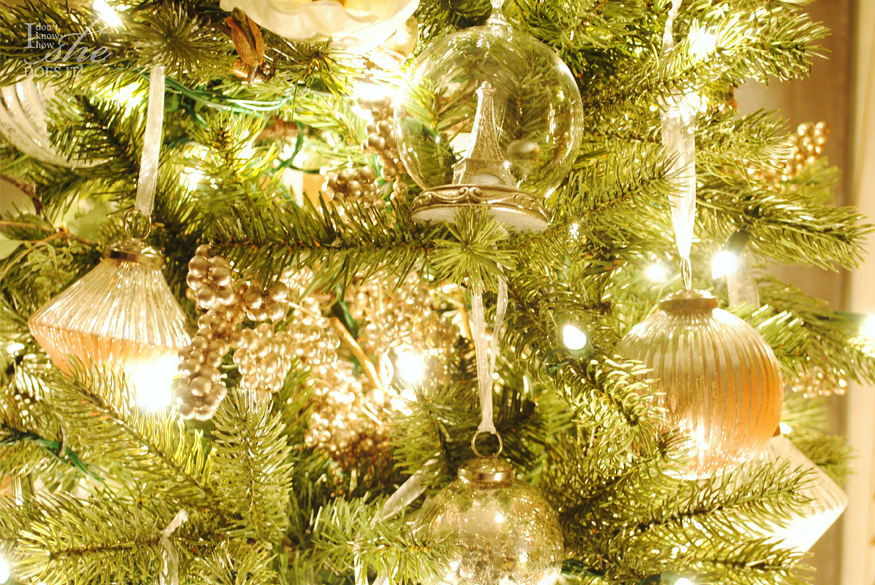 Closeup shot of a lit-up Christmas tree adorned with globe-shaped ornaments