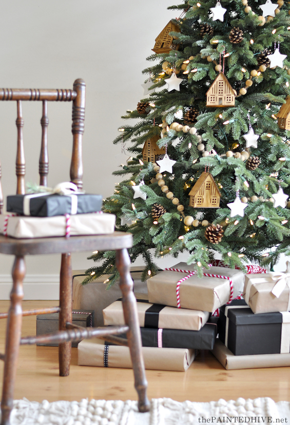 Natural and neutral Christmas tree decorated with wooden houses, garlands, and porcelain stars with Christmas gifts wrapped in black and brown kraft paper