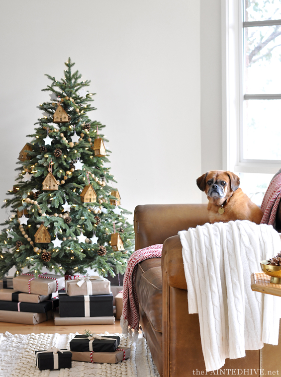 Natural and neutral Christmas tree with gifts wrapped in kraft paper in living room with couch and dog