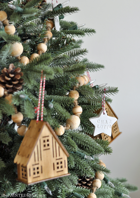 Miniature wooden houses, wooden garlands, and porcelain stars on natural and neutral Christmas tree