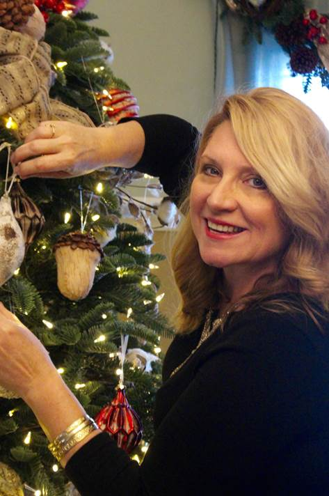 Portrait shot of a woman standing beside a Christmas tree