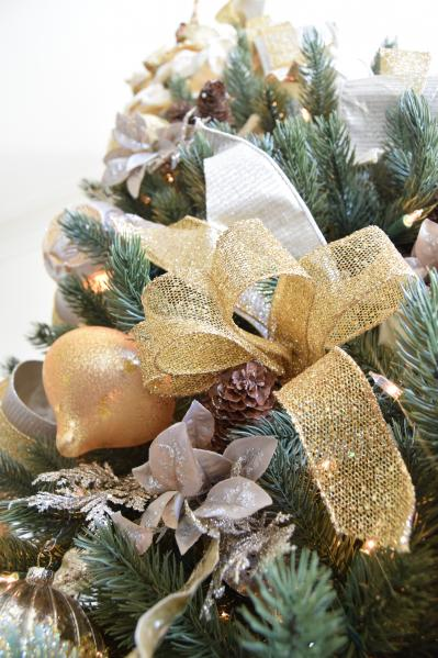 Christmas tree decorated with silver and gold ornaments and ribbon