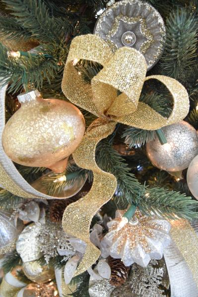Close-up of tree decorated with silver and gold ornaments