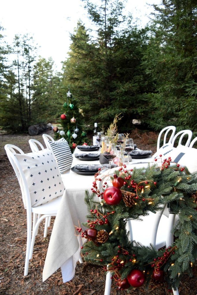 A tablescape featuring a Christmas wreath and a Christmas tree
