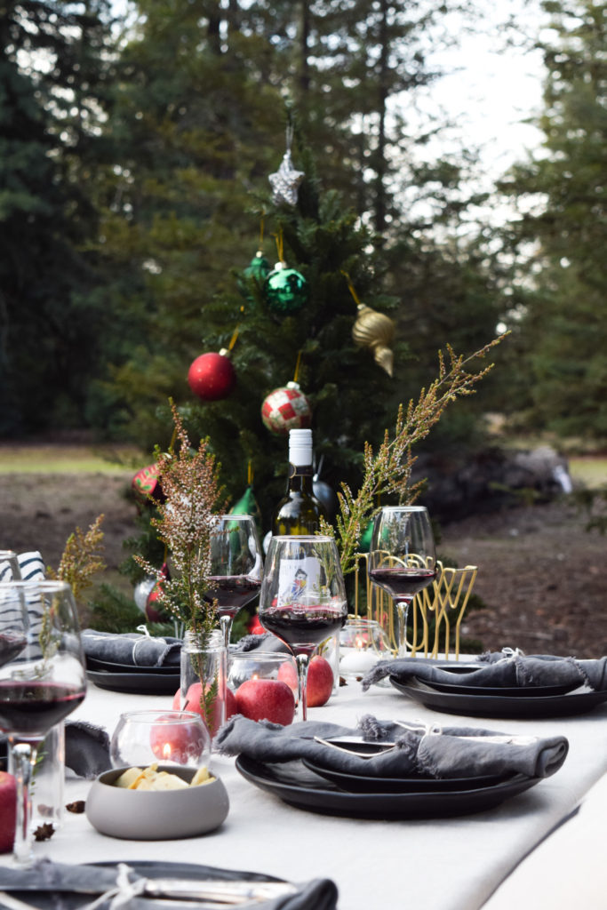 A table setting with a Christmas tree in the background