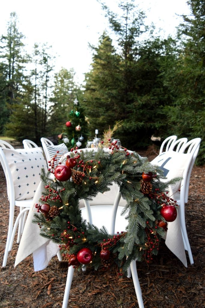 A Christmas wreath placed behind a white dining chair