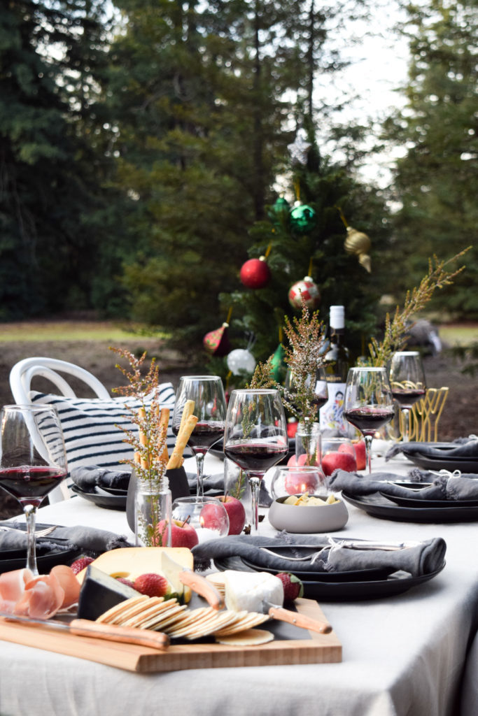 A table setting with a cheese plate, wine glasses, black plates, dark gray napkins, and a Christmas tree in the background