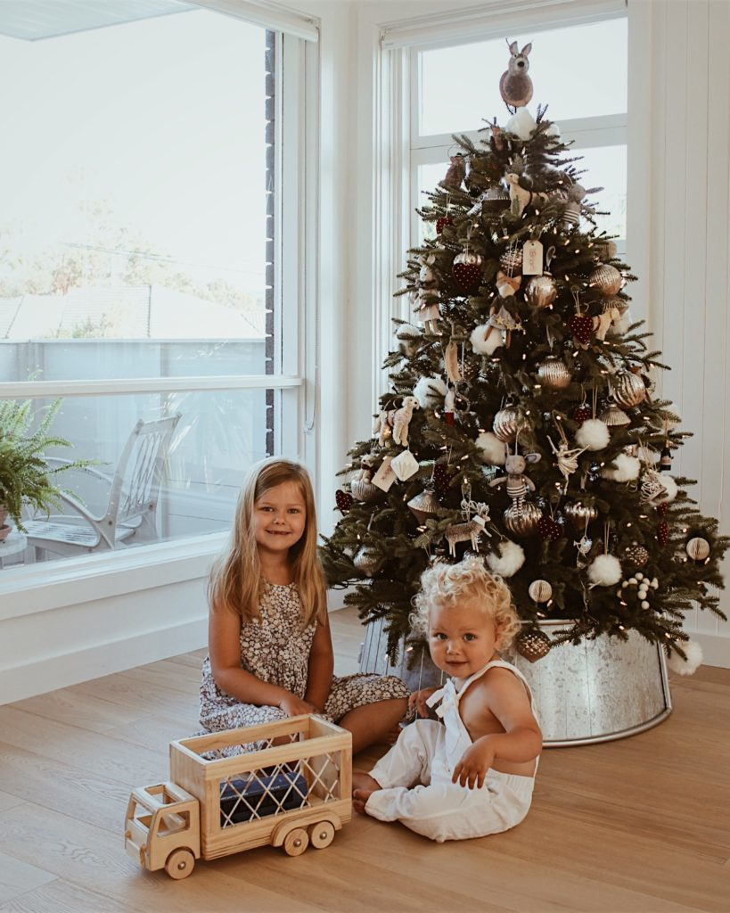 children in front of decorated fraser fir