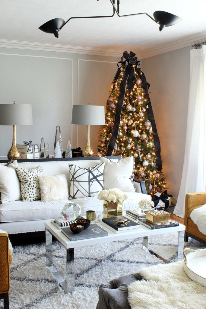 A living room with lit-up Christmas tree in a corner