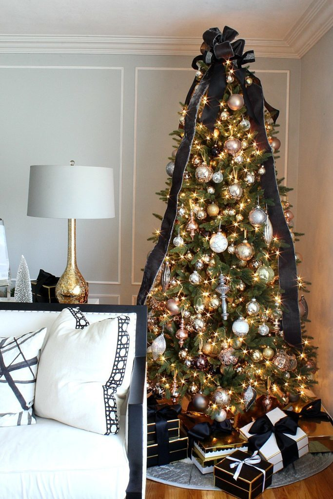 A lit-up Christmas tree decorated with assorted metallic ornaments and a black ribbon