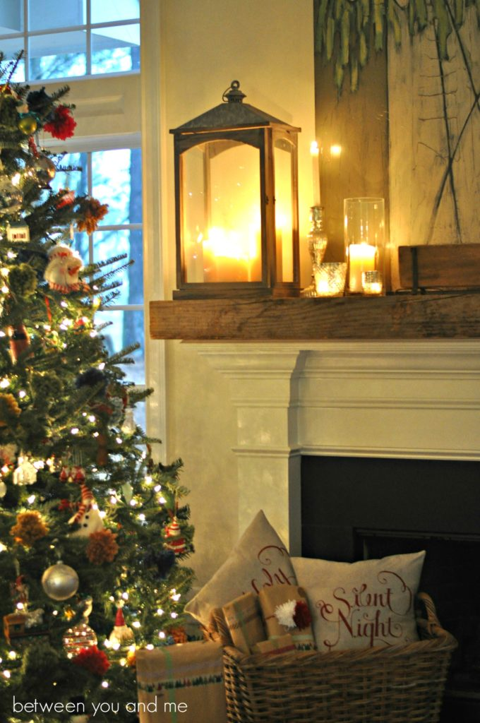 Pre-lit artificial Christmas tree beside lanterns on fireplace mantel