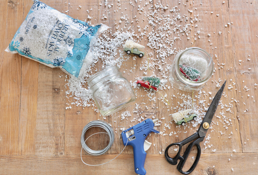 artificial snowflakes, miniature trees and trucks, mason jar, wire, glue gun, and scissors