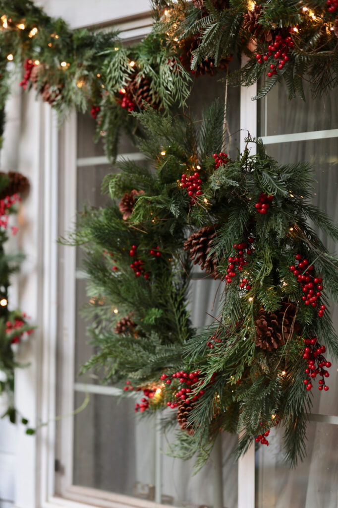 red berry pine wreath and garland hanging on window