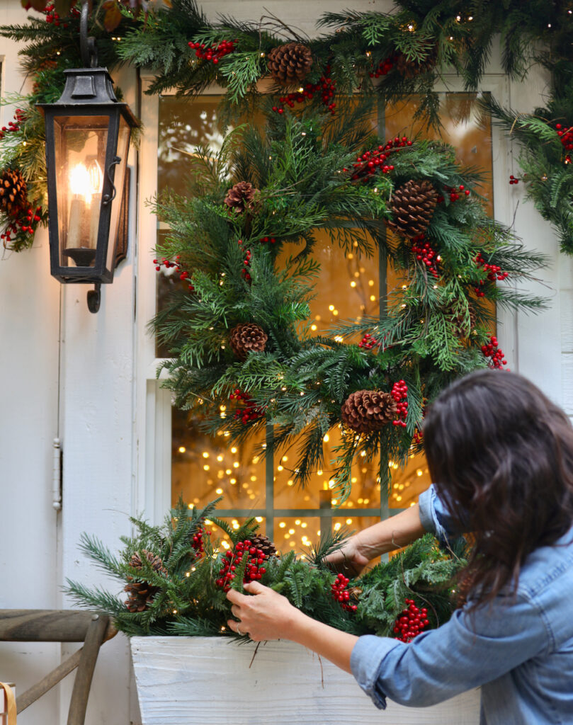 Courtney arranging garland in window box
