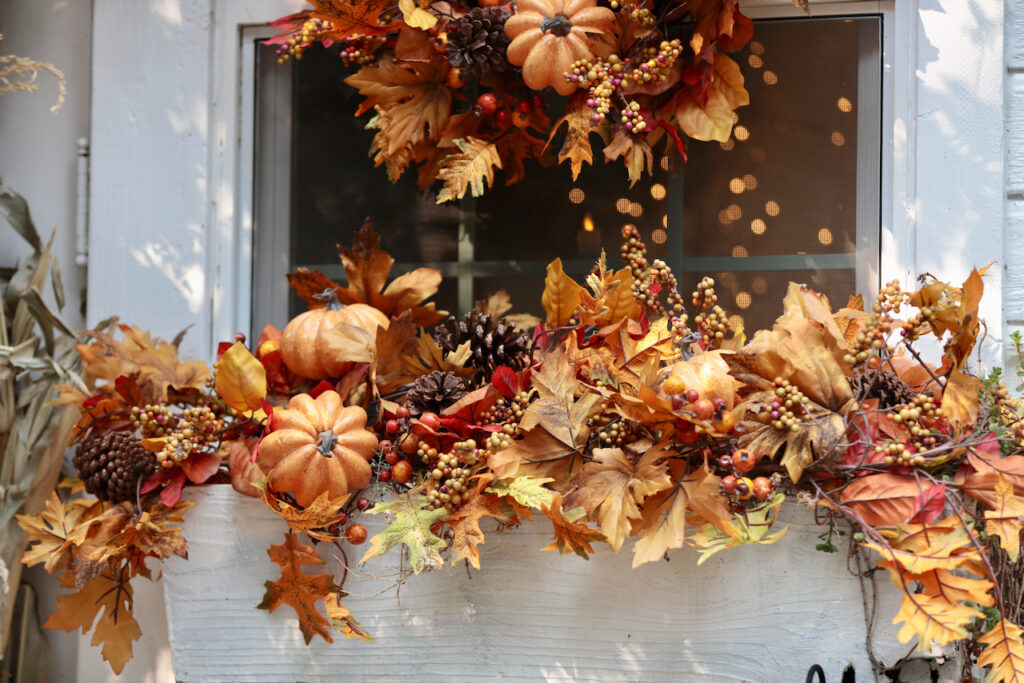 fall wreath on window with fall garland on window box